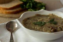 O cogumelo e as batatas desnatam a sopa na bacia branca fotos de stock royalty free