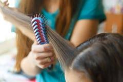 O coiffeur do cabeleireiro do close up faz o penteado fotografia de stock