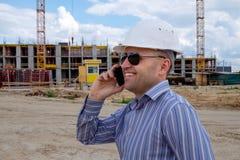 O colaborador no capacete branco no canteiro de obras fala em um telefone celular e sorri Imagem de Stock
