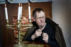 O coletor olha sua riqueza com velas iluminadas imagem de stock royalty free