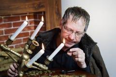 O coletor olha sua riqueza com velas iluminadas imagem de stock