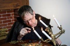 O coletor olha sua riqueza com velas iluminadas imagens de stock royalty free