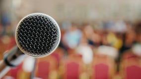 O começo da conferência, pessoa recolhe no salão No primeiro plano há um suporte com um microfone video estoque