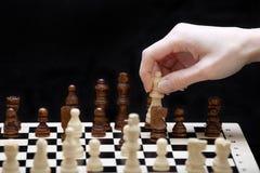 O começo de um jogo de xadrez e de uma mão Fotografia de Stock
