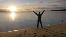 O começo do dia Um homem encontra o alvorecer na costa de um lago bonito Admira o cenário video estoque