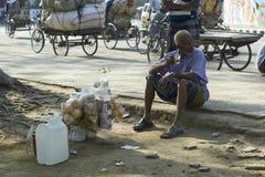 O comerciante da rua em Dhaka toma uma ruptura de chá foto de stock