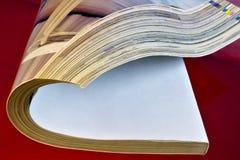 O compartimento é um periódico impresso de papel, em um fundo criativo vermelho O jornal tem um rubrication permanente e contém-n fotografia de stock