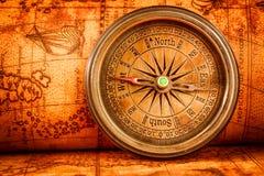 O compasso do vintage encontra-se em um mapa do mundo antigo Foto de Stock