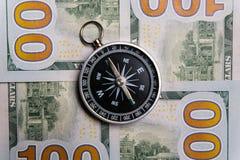 O compasso encontra-se em contas do dinheiro de cem-dólar Close-up fotografia de stock
