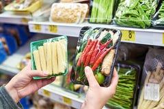O comprador escolhe legumes frescos na loja imagens de stock