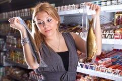 O comprador escolhe peixes fumados foto de stock