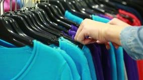 O comprador escolhe um t-shirt em um boutique filme