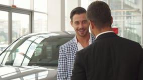 O comprador novo inspeciona o carro selecionado fotografia de stock