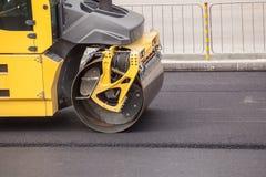 O compressor pesado do rolo da vibração no pavimento do asfalto funciona para a reparação da estrada Fotografia de Stock Royalty Free