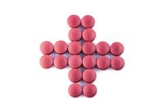 O comprimido arranjou na cruz vermelha do conceito isolada no fundo branco Fotos de Stock