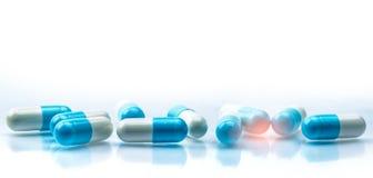 O comprimido azul e do branco das cápsulas espalhou no fundo branco com sombra e copiou o espaço conceito global dos cuidados méd fotos de stock