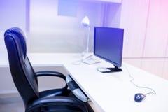 O computador está na tabela em um interior brilhante fotografia de stock
