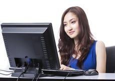 O computre asiático do PC do uso da menina para a busca e faz algo Imagens de Stock