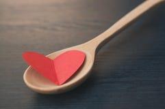 O conceito, coração de A está em uma colher de madeira como algum alimento fotos de stock