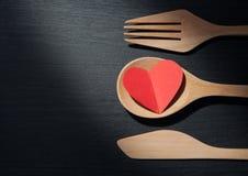 O conceito, coração de A está em uma colher, em uma forquilha e em uma faca de madeira como algum imagens de stock