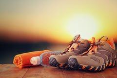 O conceito da aptidão com calçados do esporte, a toalha e a garrafa de água sobre a tabela de madeira na frente do por do sol aja Imagens de Stock