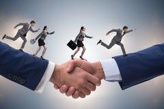 O conceito da cooperação com os povos que correm no aperto de mão Fotos de Stock Royalty Free
