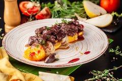 O conceito da culinária europeia Fígado grelhado da carne com fruto, a pera, a laranja e a cebola caramelizados Pratos de serviço fotos de stock