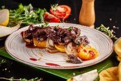 O conceito da culinária europeia Fígado grelhado da carne com fruto, a pera, a laranja e a cebola caramelizados Pratos de serviço fotografia de stock