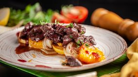 O conceito da culinária europeia Fígado grelhado da carne com fruto, a pera, a laranja e a cebola caramelizados Pratos de serviço imagens de stock royalty free
