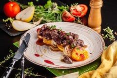 O conceito da culinária europeia Fígado grelhado da carne com fruto, a pera, a laranja e a cebola caramelizados Pratos de serviço fotos de stock royalty free