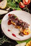 O conceito da culinária europeia Fígado grelhado da carne com fruto, a pera, a laranja e a cebola caramelizados Pratos de serviço imagem de stock