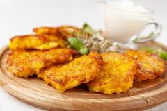 O conceito da culinária ucraniana Draniki das batatas e das abóboras, com flores comestíveis foto de stock