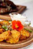 O conceito da culinária ucraniana Draniki das batatas e das abóboras, com flores comestíveis foto de stock royalty free