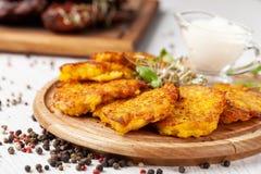 O conceito da culinária ucraniana Draniki das batatas e das abóboras, com flores comestíveis fotos de stock royalty free