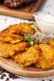 O conceito da culinária ucraniana Draniki das batatas e das abóboras, com flores comestíveis fotografia de stock