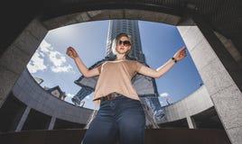 O conceito da forma urbana moderna A menina joga fora de seu revestimento da sarja de Nimes, braços aumentou altamente foto de stock