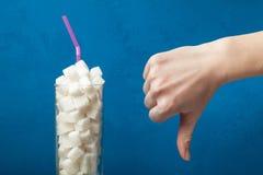 O conceito da luta contra o diabetes e do grande consumo de açúcar no alimento A mão mostra um dedo para baixo e um vidro imagens de stock