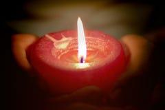 O conceito da oração e da esperança da vela ilumina-se nas mãos fotos de stock royalty free