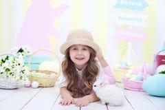 O conceito da Páscoa, dos feriados e dos povos! Menina que joga com o coelho bonito da Páscoa Decoração colorida da Páscoa, uma c imagem de stock