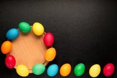 O conceito da Páscoa pintou ovos no fundo preto na fileira para o holid Foto de Stock Royalty Free
