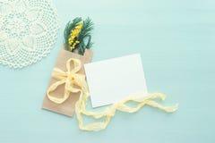 O conceito da refeição matinal internacional da mimosa do dia do ` s das mulheres no fundo azul, a curva da seda amarela com o ca Imagem de Stock Royalty Free