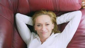 O conceito da renda passiva a mulher feliz encontra-se no sofá e nos sorrisos, sobre ela dólares de queda 4k, close-up filme