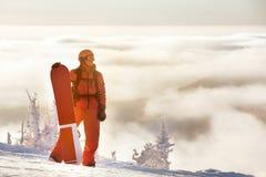 O conceito da snowboarding com homem e o snowboard contra a montanha cobrem Fotos de Stock Royalty Free