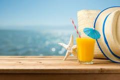 O conceito das férias das férias de verão com suco de laranja, o chapéu e o saco sobre o mar encalham Imagens de Stock