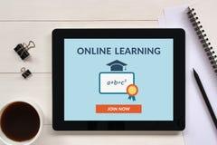 O conceito de aprendizagem em linha na tela da tabuleta com escritório objeta Foto de Stock