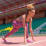 O conceito de conseguir resultados altos nos esportes ou da formação antes do campeonato Um atleta preto da menina prepara-se par fotos de stock royalty free