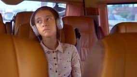 O conceito de férias de verão, curso Passeios adolescentes da menina em uma carrinha com fones de ouvido vídeos de arquivo