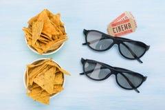 O conceito de nachos do cinema, de vidros 3D e de bilhetes para olhar o filme fotografia de stock royalty free