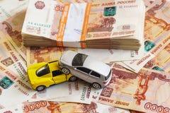 O conceito de obter o prêmio de seguro após o acidente de trânsito: dois carros e uma pilha de rublos de russo na operação bancár Foto de Stock
