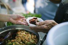 O conceito de problemas da vida, fome na sociedade: conceito do alimento da caridade para os pobres: Mão-alimentação ao carente n imagem de stock